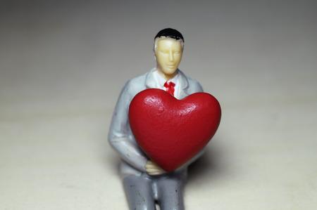 Photo pour Miniature man with business suit holding red heart - image libre de droit