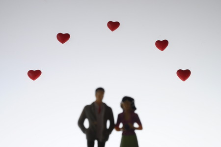 Photo pour Figurine of couples of lovers and red hearts background - image libre de droit
