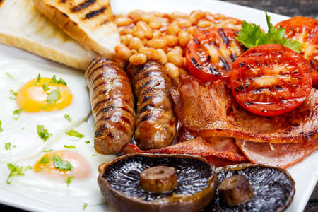 Photo pour Full English breakfast with bacon, sausage, fried egg, baked beans and mushrooms. - image libre de droit