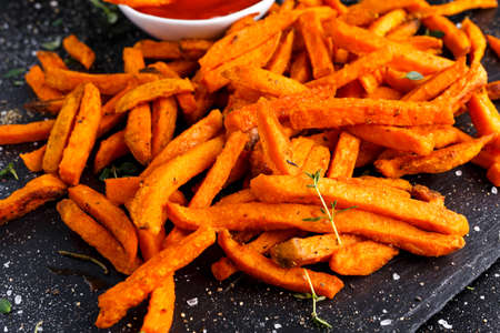 Healthy Homemade Baked Orange Sweet Potato Fries with Ketchup, herbs, salt and pepper