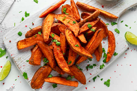 Photo pour Healthy Homemade Baked Orange Sweet Potato wedges with fresh cream dip sauce, herbs, salt and pepper. - image libre de droit