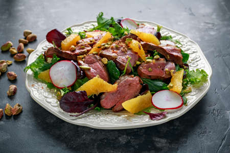 Foto de Duck breast fillets steak salad with orange halves, radishes and crushed pistachios - Imagen libre de derechos