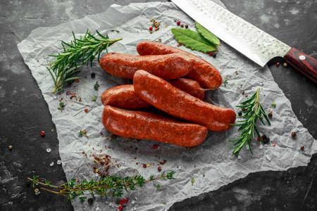 Foto de Freshly made raw breed butchers sausages in skins with herbs on crumpled paper. - Imagen libre de derechos