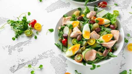 Foto de Healthy Nicoise salad with salmon, colourful sweet cherry tomatoes, olives, green beans, cucumber ribbons, soft boiled eggs, water-cress leaves with Mediterranean seasoning - Imagen libre de derechos