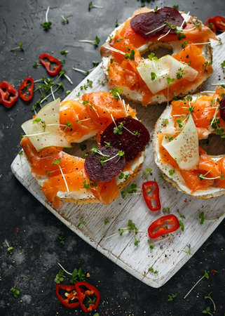 Smoked salmon bagel toasts with soft cheese, cucumber ribbons and beetroot and dill, cress salad
