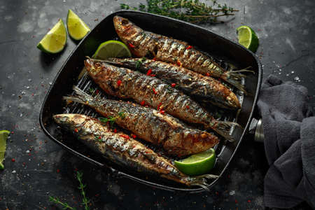 Foto de Grilled sardines with thyme, chili and lime wedges on cast iron skillet - Imagen libre de derechos