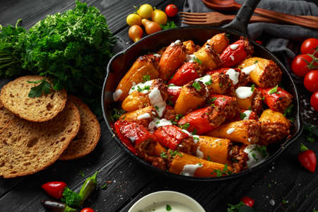 Photo for Sausage meat, mince and rice Stuffed sweet mini bell peppers baked in cast iron skillet, pan topped with yogurt and fresh parsley - Royalty Free Image