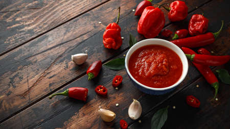 Photo pour spicy hot sweet chili sauce with mix of chilli pepper, garlic and tomatoes on rustic wooden background - image libre de droit