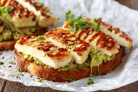 Photo pour Avocado and grilled haloumi cheese toast with nigella and sesame seeds on crumpled paper. healthy breakfast - image libre de droit