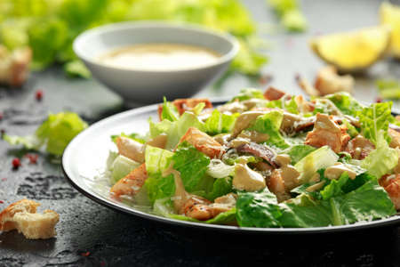 Foto de Caesar salad with chicken, anchous fish, croutons, parmesan cheese and greens. healthy food - Imagen libre de derechos