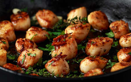 Photo pour Scallops seared in garlic and parsley butter served in cast iron skillet - image libre de droit