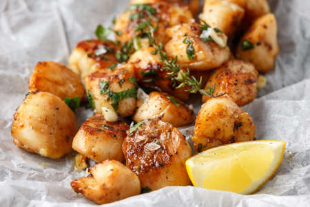 Photo pour Scallops seared in garlic and parsley butter served on crumpled paper - image libre de droit