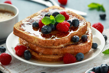 Photo pour French cinnamon toast with blueberries, raspberries, maple syrup and coffee. morning breakfast - image libre de droit
