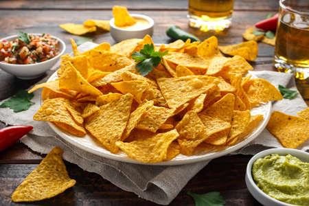 Foto de Tortilla nachos chips with cheese sauce, guacamole and tomatoes salsa dip. glass of beer. - Imagen libre de derechos