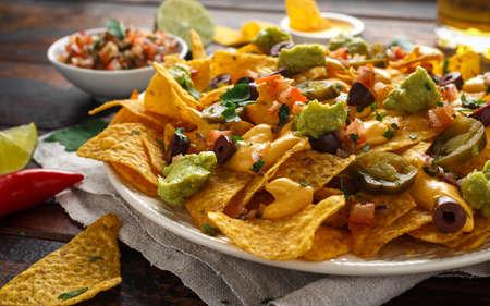 Foto de Mexican nachos tortilla chips with olives, jalapeno, guacamole, tomatoes salsa, cheese dipand beer. - Imagen libre de derechos