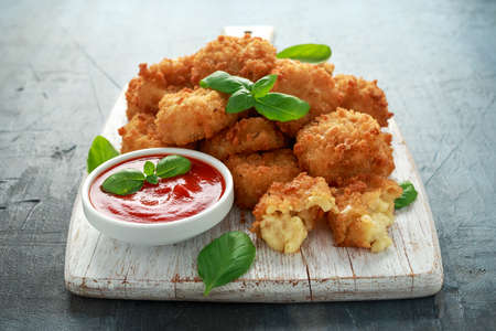Photo for Fried Mac, macaroni and Cheese Bites in breadcrumbs with ketchup sauce on white wooden board - Royalty Free Image
