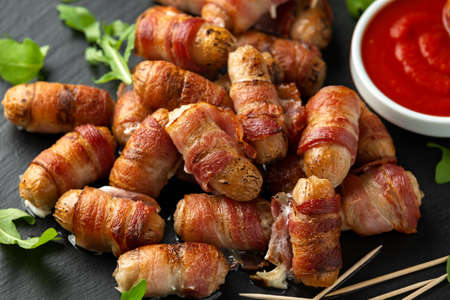 Photo pour Party finger food pigs in blankets on toothpicks with ketchup sauce and wild rocket leaves. - image libre de droit