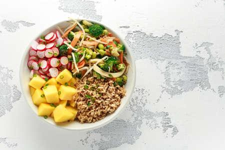 Photo pour Asian style Vegan salad bowl with edamame, vegetable stir-fry mix, wholegrain rice, quinoa, mango chunks drizzled with mango, chilli dressing - image libre de droit