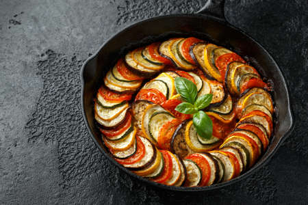 Foto de Ratatouille Vegetable Stew with zucchini, eggplants, tomatoes, garlic, onion and basil. on cast iron pan. Traditional French food - Imagen libre de derechos