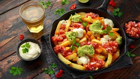 Foto de Loaded potato nachos with melted cheddar cheese, sour cream, tomato salsa, chilli, guacamole and beer - Imagen libre de derechos