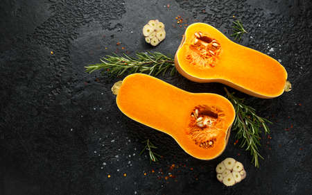 Photo for Fresh Butternut squash with rosemary, garlic, chilli flake and salt on black rustic background - Royalty Free Image