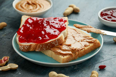 Photo for Peanut Butter and strawberry Jelly Sandwich in a blue plate. morning breakfast. - Royalty Free Image