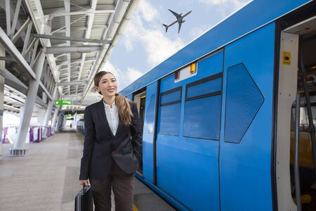 Photo pour Young beautiful Asian businesswoman holding a bag and waiting for the train to arrive at airport rail link skytrain station. - image libre de droit