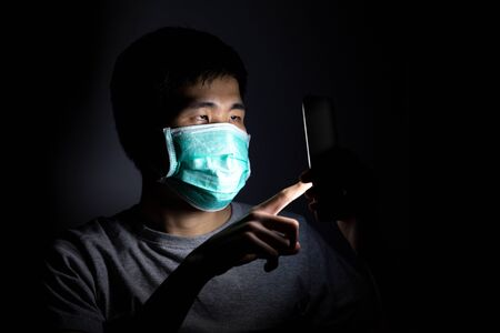 Foto de Asian man using smart phone work from home and wear a protective medical mask to prevent Coronavirus (CoVID-19) outbreak. - Imagen libre de derechos
