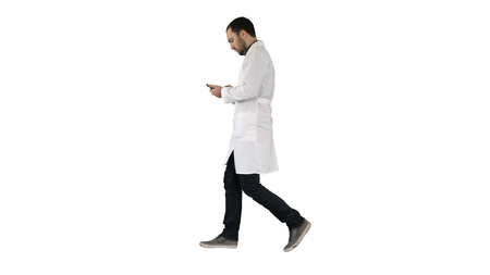 Photo pour Male doctor walking and using mobile phone on white background. - image libre de droit