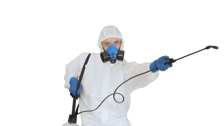Photo pour Man wearing an NBC personal protective equipment spray disinfectant and dancing on white background. - image libre de droit
