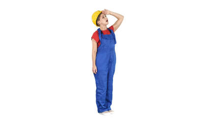 Photo pour Engineer woman in yellow helmet looking up amazed at a building or statistics or graph on white background. - image libre de droit