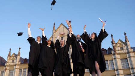 Photo pour Group of diverse graduation students throwing their mortarboards - image libre de droit