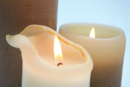 Close up of two burning candles in beige and ivory white