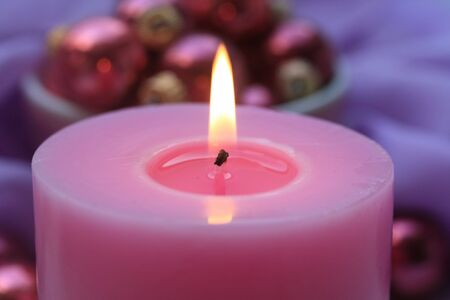 Pink candle with pink christmas decorations on background