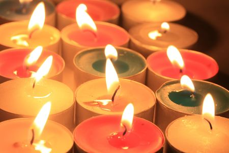 A collection of burning votive candles in various colors
