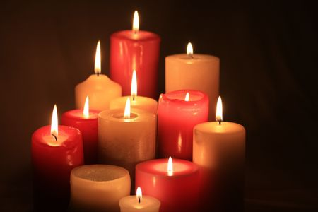 A group of burning candles, different sizes in red and white