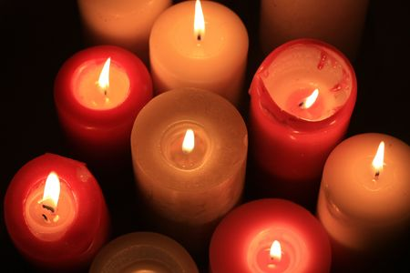 A group of burning candles in different colors