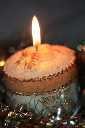 A burning gold decorated christmas candle and other golden christmas decorations
