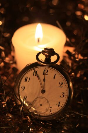 A vintage pocket watch in the candlelight, counting down for the new year