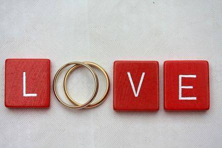 Red wooden letters with simple plain wedding bands.