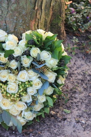 Heart shaped sympathy flower arrangement with white roses near a tree