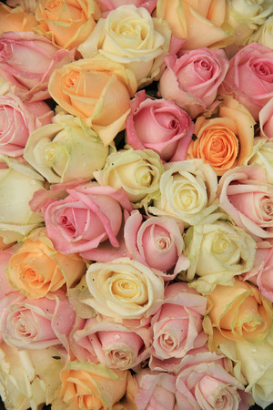 Pastel roses in various colors in a mixed wedding arrangement