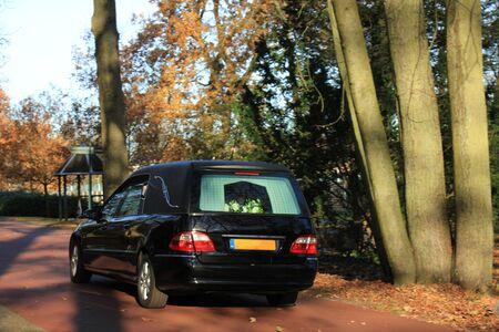 Photo pour A black hearse on a cemetery in the autumn - image libre de droit