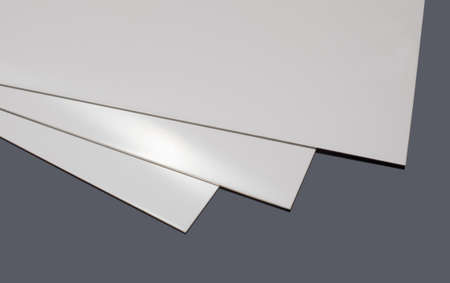 three stainless steel sheets, on a black surface