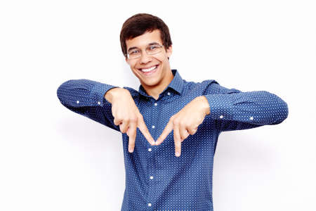 Young hispanic man wearing blue shirt and glasses showing M sign with his fingers and smiling against white wall - cities starting with M concept