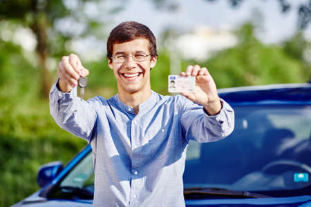 Young hispanic man wearing glasses and blue jeans shirt holding in his hands car keys and driving license against car outdoors - new drivers concept