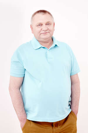 Photo pour Mature cheerful man wearing blue shirt and brown trousers standing with hands in pockets and smiling against white wall - casual dress code concept - image libre de droit