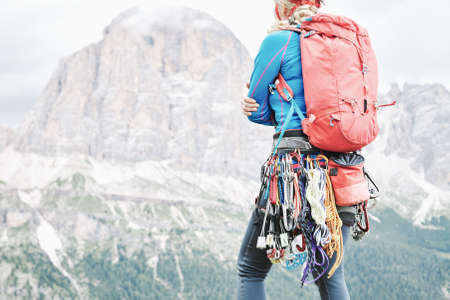 Photo for Female mountaineer with trad climbing rack including backpack, helmet, chalk bag, harness with spring-loaded cams, nuts, quickdraws, slings and carabiners preparing for ascent in summer Dolomite Alps - Royalty Free Image