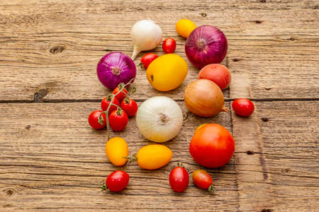 Autumn harvest vegetables cooking background. Assortment of different types onions and tomatoes. Old vintage wooden boards background, copy space