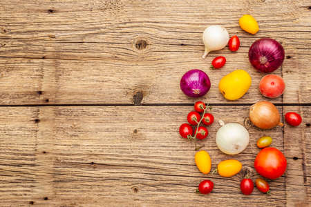 Autumn harvest vegetables cooking background. Assortment of different types onions and tomatoes. Old vintage wooden boards background, copy space, top view